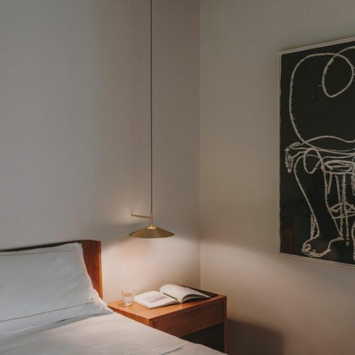 Henri wall light gold installed beside a bed