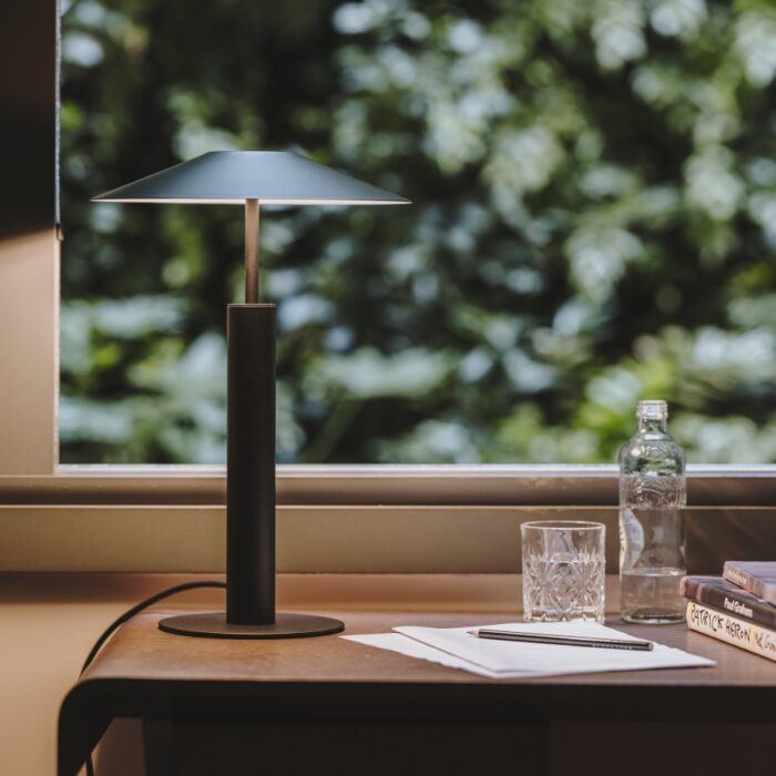 Henri table lamp in black on a timber desk in a home office