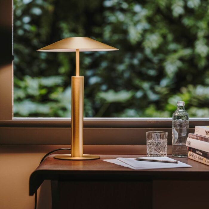 Henri table lamp in gold on a timber desk in a home office