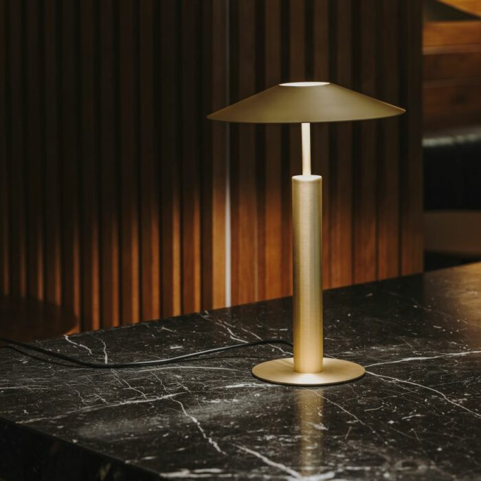 Henri table lamp in gold on a dark marble table