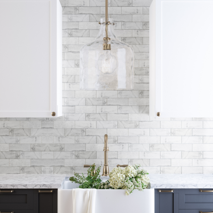 Water glass pendant light above kitchen sink in front of tiled wall